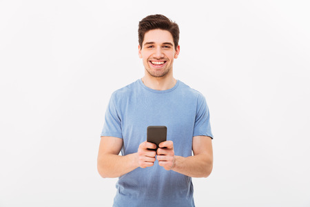 Photo pour Happy man 30s in casual t-shirt typing sms or browsing internet using mobile phone isolated over white background - image libre de droit