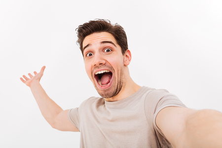 Photo for Photo of excited man in casual t-shirt and bristle on face screaming in happiness while taking selfie isolated over white background - Royalty Free Image