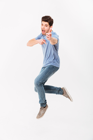Photo for Full-length photo of handsome man 30s in casual t-shirt and jeans having fun and pointing index fingers on camera isolated over white background - Royalty Free Image
