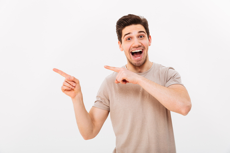 Photo for Excited man in casual t-shirt rejoicing and pointing fingers aside on copyspace text or product isolated over white background - Royalty Free Image