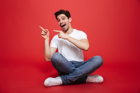 Portrait of a joyful young man in white t-shirt sitting on a floor and pointing fingers away isolated over red background
