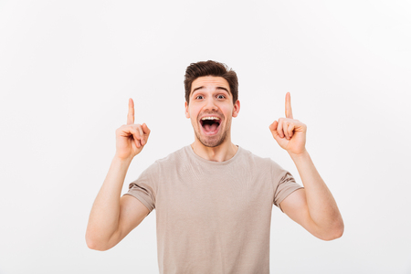 Image of optimistic man in casual t-shirt smiling and pointing fingers upwards on copyspace text or product isolated over white background