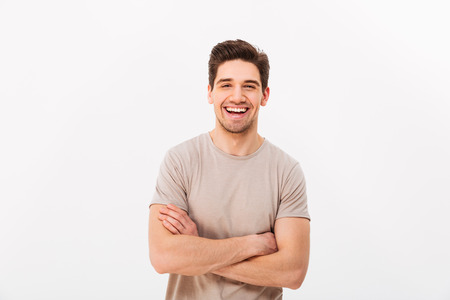 Photo for Image of happy smiling man 30s with bristle posing on camera with hands crossed isolated over white background - Royalty Free Image