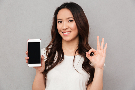 Photo for Closeup photo of chinese woman in casual t-shirt demonstrating copyspace screen of modern smartphone and showing ok sign isolated over gray background - Royalty Free Image
