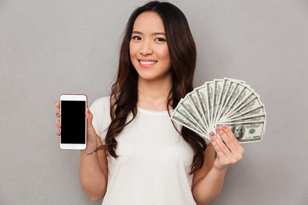 Portrait of asian lucky woman 20s holding fan of money dollar banknotes and demonstrating copyspace screen of cell phone isolated over gray background