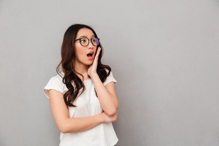 Photo pour Shocked asian woman in t-shirt and eyeglasses holding her cheek and looking away over black background - image libre de droit