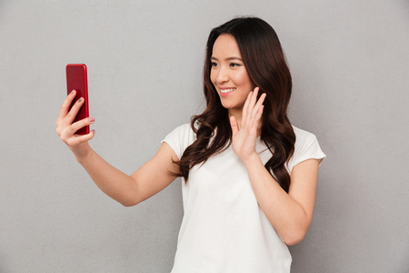 Photo pour Sociable beautiful woman with asian appearance taking selfie or speaking on video call using cell phone isolated over gray background - image libre de droit