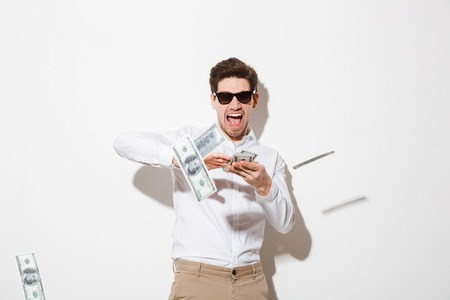 Foto de Portrait of a happy young man in sunglasses throwing money banknotes at camera isolated over white background - Imagen libre de derechos