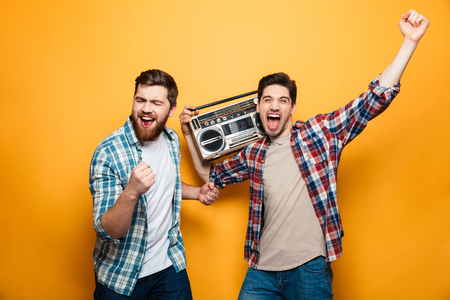 Two playful men in shirts listening music by record player while rejoices and looking at the camera over yellow background