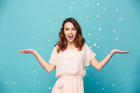 Foto de Portrait of a happy beautiful girl wearing dress standing standing under confetti rain and celebrating isolated over blue background - Imagen libre de derechos