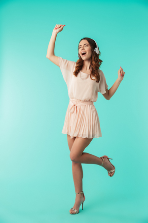 Photo for Full length portrait of a happy young girl in dress listening to music with headphones and dancing isolated over blue background - Royalty Free Image