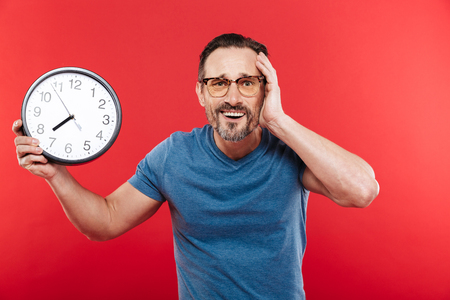 Portrait of an adult confused man in colorful sunglasses standing isolated over red background looking camera holding clock.