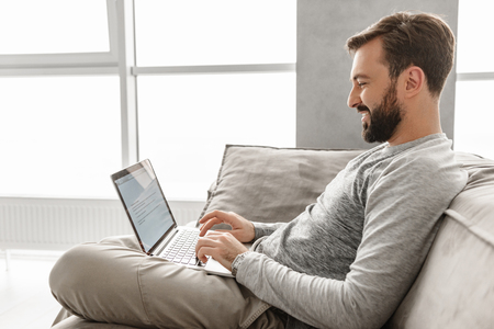 Photo in profile of happy bearded man 30s in casual clothing working or browsing internet on laptop in modern apartment