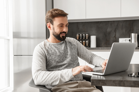 Picture of successful man 30s in casual wear sitting alone in modern apartment and using laptop