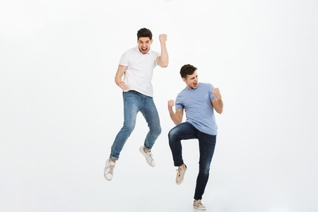 Photo pour Full length portrait of two happy young men jumping and celebrating success isolated over white background - image libre de droit