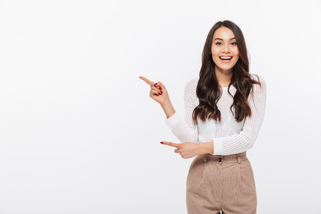 Portrait of a happy asian businesswoman pointing finger away at copy space isolated over white background