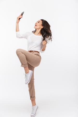 Photo pour Full length portrait of an excited asian businesswoman celebrating with mobile phone isolated over white background - image libre de droit