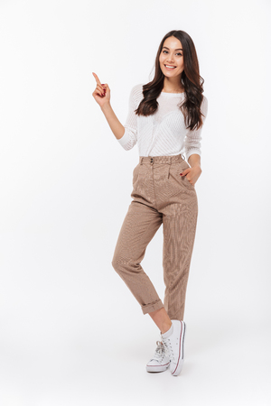 Foto de Full length portrait of a smiling asian businesswoman pointing finger away isolated over white background - Imagen libre de derechos
