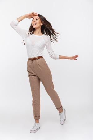 Foto de Portrait of a smiling asian businesswoman looking far away isolated over white background - Imagen libre de derechos