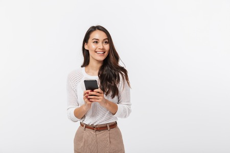 Portrait of a happy asian businesswoman holding mobile phone and looking away isolated over white background