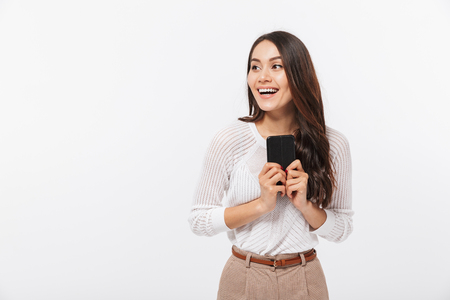 Photo pour Portrait of a happy asian businesswoman using mobile phone and looking away isolated over white background - image libre de droit