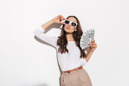 Photo pour Portrait of a confident young asian businesswoman in sunglasses showing money banknotes and celebrating isolated over white background - image libre de droit