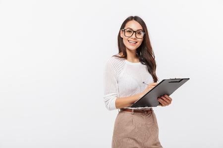 Foto de Portrait of a happy asian businesswoman holding clipboard isolated over white background - Imagen libre de derechos