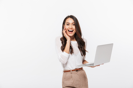 Portrait of an excited asian businesswoman holding laptop computer isolated over white background