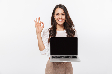 Foto de Portrait of a smiling asian businesswoman holding blank screen laptop computer and showing ok isolated over white background - Imagen libre de derechos