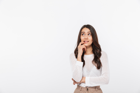 Portrait of a worried asian businesswoman looking up at copy space isolated over white background