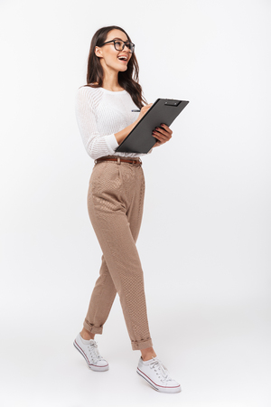 Foto de Full length portrait of a happy asian businesswoman holding clipboard while walking isolated over white background - Imagen libre de derechos