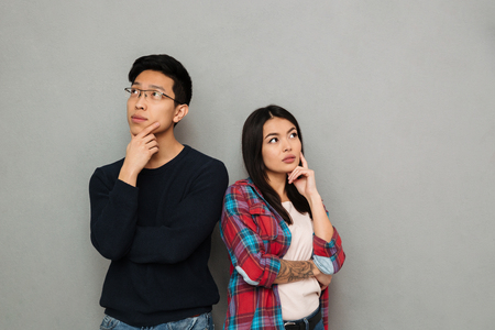 Photo pour Image of thinking serious young asian loving couple standing isolated over grey wall background looking aside. - image libre de droit