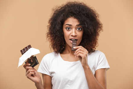 Photo pour Portrait of a cheerful young african woman eating chocolate bar isolated over beige background - image libre de droit