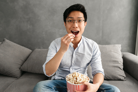 Photo pour Portrait of a happy young asian man eating popcorn while sitting on a couch at home and watching TV - image libre de droit