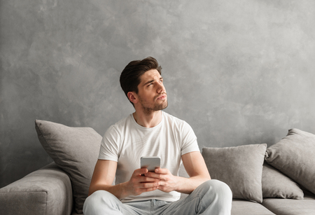 Image of man in basic t-shirt holding cell phone in hands and looking aside with brooding gaze while sitting on couch in living room