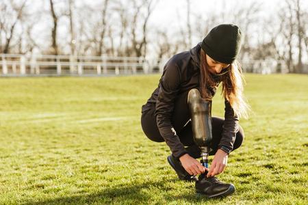 Foto de Image of young handicapped sportswoman in tracksuit squatting and tying shoelaces on prosthesis leg outside - Imagen libre de derechos