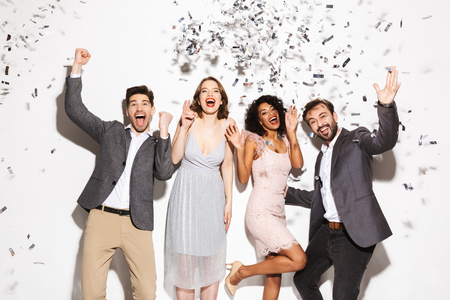 Group of happy well dressed multiracial people dancing together under confetti rain isolated over white background