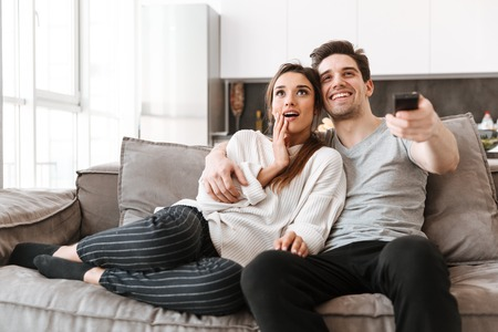 Photo pour Portrait of a happy young couple relaxing on a couch at home while watching TV - image libre de droit