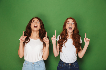 Portrait of two pretty women with red hair in white t-shirts smiling and pointing fingers upward in excitement isolated over green background