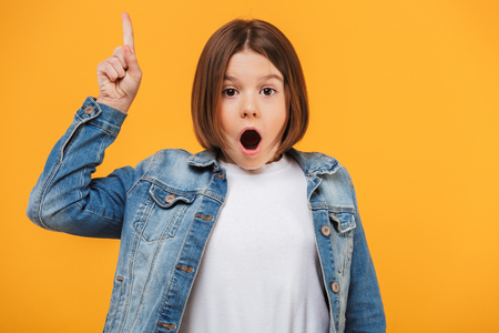 Photo pour Portrait of an excited little schoolgirl pointing finger up over yellow background - image libre de droit