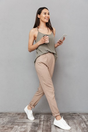 Foto de Full length portrait of a pretty asian woman holding takeaway coffee cup and using mobile phone while walking isolated over gray background - Imagen libre de derechos