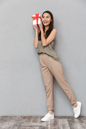 Foto de Full length portrait of a pretty young asian woman holding present box over gray background - Imagen libre de derechos