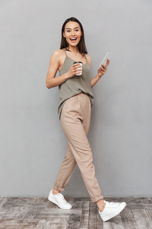 Full length portrait of a smiling asian woman holding takeaway coffee cup and using mobile phone while walking isolated over gray background