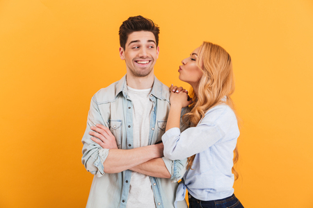 Photo pour Portrait of young lovely people in basic clothing expressing love and affection while woman kissing man on cheek isolated over yellow background - image libre de droit
