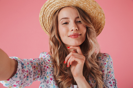 Close up portrait of a pretty young woman in summer dress and straw hat taking a selfie isolated over pink background