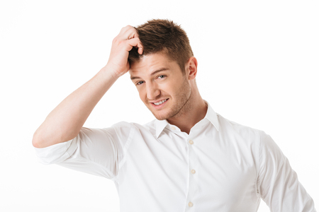 Photo pour Portrait of a confused young man scratching his head isolated over white background - image libre de droit