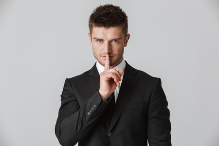 Photo pour Portrait of a confident young businessman in suit showing silence gesture isolated over gray background - image libre de droit