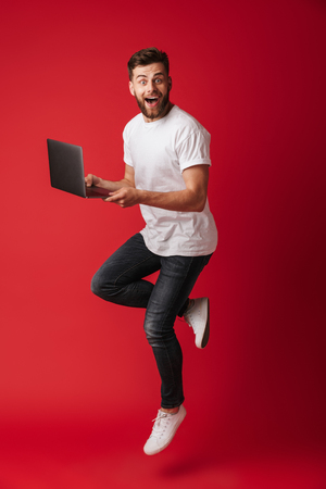 Foto de Image of surprised young man jumping isolated over red wall background using laptop computer. Looking camera. - Imagen libre de derechos