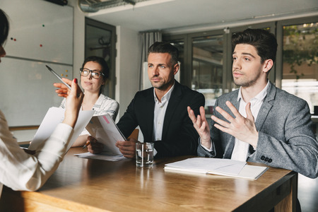 Business, career and placement concept - three executive directors or head managers sitting at table in office and negotiating with new personnel during interview