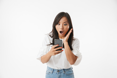 Photo for Image of shocked or surprised asian woman screaming and gesturing in panic, while looking at smartphone isolated over white background - Royalty Free Image